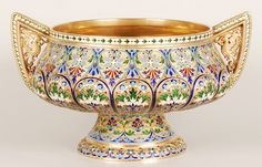 "A Russian silver gilt and cloisonne enamel 2 handled punch bowl on a circular pedestal base, workmaster Antip Kuzmichev, stamped ""Made for Tiffany and Co""., Moscow, late 19th century. Enameled with polychrome roundels and scrolling foliate motifs against a gilt ground. The pointed handles pierced with fanciful birds."