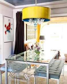 Love this statement-making crystal-tipped teal and yellow pendant light paired with the modern glass dining table and timeless tufted benches.
