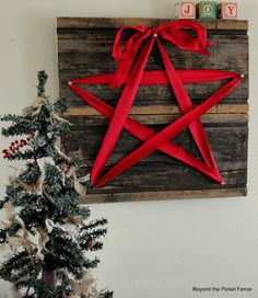 A rustic Christmas decoration with a red star ribbon on reclaimed wood http://bec4-beyondthepicketfence.blogspot.com/2012/11/12-days-of-christmas-day-8.html