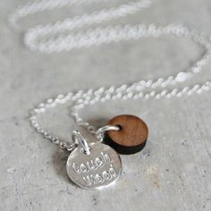 """The chain holds a silver charm imprinted with """"touch wood"""" along with a small disc of walnut. £43.00"""