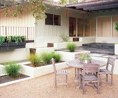Select a Style - Create a high-end modern feel by ultizing contemporary style.  -- Stair-stepped planters hold architectural grasses.  -- A water feature echoes the planters' shapes, repeating the theme.  -- A gravel patio helps break up the white-painted concrete blocks.