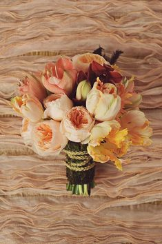 Variegated parrot tulips pair well with deep-toned amaryllises, and peach-colored Juliet garden roses.