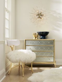Swanky metal side chair channels Hollywood Regency styling with a curvaceous gold-leafed metal frame, upholstered seat and back rest, and posh sheepskin pouf on the seat.
