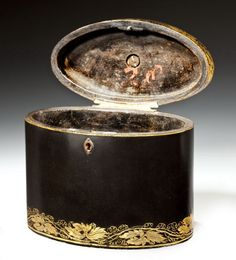 A Regency papier mache oval tea caddy with gilt leaf banding, the hinged top with brass loop handle and trailing leaf border.