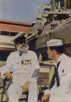 In 1899 Louis Little fought with Commodore Dewey's forces in Manila Bay. This experience was one the high spots in Chief Petty Officer Little's life, which has been around the Navy for 64 of his 80 years. He enlisted in 1889 & retired from active duty in 1919 as a chief quartermaster. At 68 he reported for duty when the Japanese invaded the islands. Fighting as a guerrilla, he was captured in 1943. Here at the Olongapo Naval Base on Subic Bay a petty officer talks to the chief.