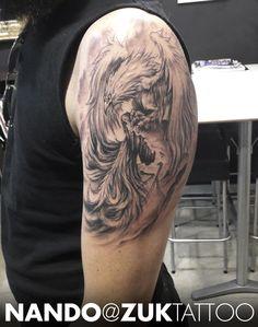 Tatuaje en negro y gris de un Fénix en el brazo.