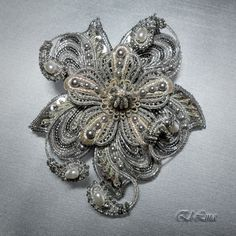 """Вышитая брошь """" В серебре"""" Брошь выполнена в смешанной технике: золотное шитьё, вышивка бисером и игольное кружево. Диаметр: 8,5 - 9 см. Каждый элемент броши был вышит и выплетен по отдельности, а затем собран в цветок. Материалы:шнуры - 3 вида, жемчуг Сваровски, чешские бусины под жемчуг, пайетки, 3 вида и оттенка металлизированных нитей, бисер MIYUKI и TOHO № 15."""