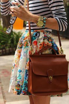 """O look fica sempre mais interessante com mix de estampas. As listras deixam a saia rodada florida menos romântica e """"menininha"""" e a bolsa de couro quadrada traz um ar mais masculino."""