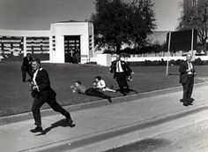 """Moments after the assassination, photographers dash after the motorcade, while Bill and Gayle Newman stay on the the ground with their children. """"I had never been around gunfire, so it was quite a shock to see someone shot in the head. … And it was the president of the United States,"""" Gayle Newman said."""