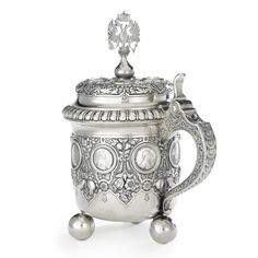 A MASSIVE FABERGE SILVER TANKARD, WORKMASTER STEPHAN WAKEVA, ST. PETERSBURG, CIRCA 1890 mounted with various 18th and 19th century coins and medallions, chased with fruit and foliage on a matted ground, raised on three ball feet, with C-scroll handle and the finial in the form of the Imperial eagle, marked with initials of workmaster, K. Faberge in Cyrillic with Imperial warrant and 84 standard, also with scratched inventory number 3212