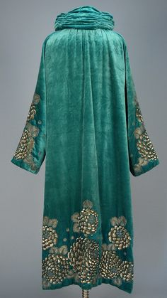 SEQUINED VELVET EVENING COAT, 1923. Turquoise silk having ruched and padded stand collar, decorated on sleeve and at hem with a stylized floral in platinum sequins and metallic cord embroidery, silk lining.