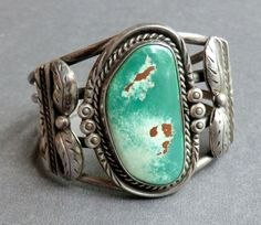 Fabulous vintage turquoise cuff bracelet with a large turquoise stone and beautiful silver artistry. The cuff is artist signed EN and is most likely…