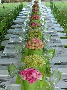 green and pink wedding table with a touch of yellow in the flowers and complimentary chairs and table runner.  White linens and simple plates help to balance this colorful setting.  Great for spring or summer wedding.