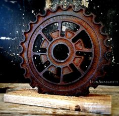"""Very old gear of thick cast iron in an ornate industrial design. Rare, Z-style spoke design. Engraved text and numerals to make it even more intriguing! Rustic reclaimed lumber display stand.7 5/8"""" diameter.Purchase 2 or more of these 8"""" sculptures, and your order ships domestically for free. Free international shipping on the 2nd 8"""" gear sculpture purchased when shipped together."""