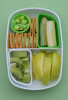 sliced green apple andkiwi fruit on the bottom; pickles, Wheat Thin crackers with green cream cheese, a little lucky silicone cup of green treats in the corner (gold coins, green gummy worm, green Skittles).