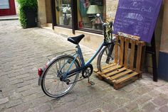 """bike, recycled pallet, stand, upcycled A bicycle stand made with an old pallet cutted in two parts. It's for a book shop """"La Mère Lison"""" (in France) where everything is made with old and recycled things.   More information: La Mère Lison website ! Submitted by: aurore halpert !"""