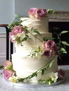 Rustic buttercream wedding cake dressed with fresh dusky pink roses and freesias