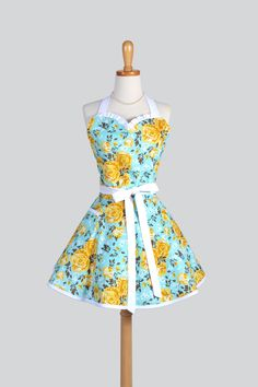 Quintessential vintage yellow and turquoise rose floral will remind you of days gone by. Tailored in a Sweetheart retro hostess apron style reminiscent of aprons worn in the 50's and 60's with a full
