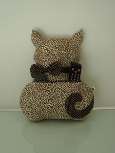 Almofada porta controle remoto no formato de oncinha feita em tecido 100% algodão e com enchimento super macio anti alérgico.    **Medida: 38cm de altura X 34cm de largura**  **Controles NÃO acompanham a almofada** R$ 47,00 Cat Crafts, Crafts To Sell, Sewing Crafts, Diy And Crafts, Sewing Projects, Eyelash Pillow, Creation Couture, Sewing Pillows, Family Crafts