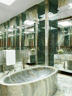 Èle Garzouzi's mirrored bath features a massive tub of carved Iranian titanium travertine; Antonio Citterio fittings by Axor | archdigest.com