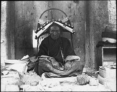 Photographer:  Sir Charles Bell or Rabden Lepcha?,  Collection:  Sir Charles Bell,  Date of Photo:  1904 – 1921, Region:  Gyantse Bazaar.  The richest trader in Gyantse sitting at her stall in the market, wearing a headdress and neck ornament of beads.