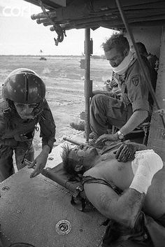 08 Apr 1972, Lai Khe, South Vietnam --- Covered with blood, two American advisers are placed aboard a helicopter here April 8th after they were wounded when North Vietnamese overran the Loc Ninh area. The light observation braved intense enemy fire to rescue the Americans and six South Vietnamese soldiers out. --- Image by © Bettmann/CORBIS