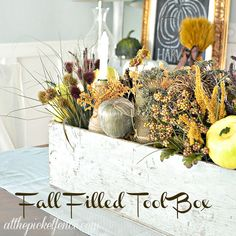 Turn a vintage tool box into a frugal fall centerpiece with Dollar Store pumpkins, fall foliage and twine wrapped wine bottles!