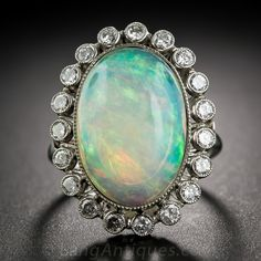 Esta hermosa joya cuenta con una vibrante 7 quilates ópalo ovalada que brilla intensamente con la paleta de un pintor de azul, verde y ardientes destellos naranja flotando dentro de un marco brillante de 3/4 de un quilate de espumosos ronda diamantes talla brillante. Hechos a mano en platino brillante, con detalles encantadores, como una galería de encaje, los hombros de diamantes de perlas-set y delicado milgrain grabado. En un tamaño de dedo 6 3/4.