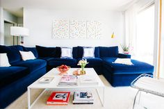 Love this navy velvet sofa, coffee table styling, and polka dot art. From the apartment tour of Jeanne Chan of Shop Sweet Things