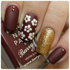 Floral nail art: deep brownish red nails, daisies, gold glitter accent nail…