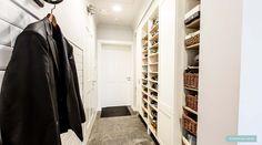 Garderoba łączy garaż z pralnią i holem wejściowym. Kamienne płyty z grafitowego marmuru są wyjątkowo odporne na codzienne zabrudzenia. Otwarty regał  mieści obuwie domowników. Projektowanie Wnętrz - Architekt Poznań