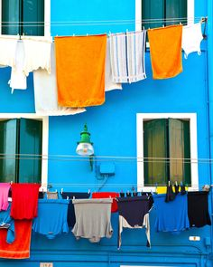 Burano photograph: A blue house with white window frames and green shutters, and colorful laundry drying on the line.The mix of colors is typical of what you can see on this beautiful island a few…MoreMore Green Design, Italian Colors, Green Shutters, Hanging Clothes, Window Frames, Blue Walls, Color Mixing, Shabby Chic, Windows