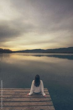 Back view of woman sitting at the lakeshore. by Eduard Bonnin - BONNINSTUDIO
