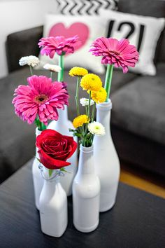 Spray paint vases or old Coca Cola bottles white to keep a clean color scheme where the flowers can draw the attention!