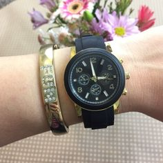 "Black & Gold Watch Black & Gold watch with a rubber wrist band and gold plated base. The metal is lead and nickel free. Hook and loop buckle. Watch face has a 1.5"" diameter. Adjustable up to approximately 8"". Also available in white. T&J Designs Accessories Watches"
