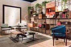 Ambiente decorado para a mostra Modernos e Eternos com tons neutros, poltrona azul, sofá branco, tapete cinza, quadros e plantas na decoração.