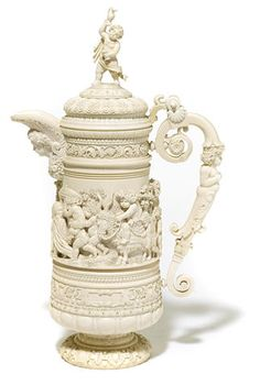 A fine and large German carved ivory tankard late 19th century  - The hinged lid surmounted by a figural finial, centered by a continuous panel of a procession of putti at play in a wooded landscape, flanked by a scroll handle carved with a putto herm, on circular foot.