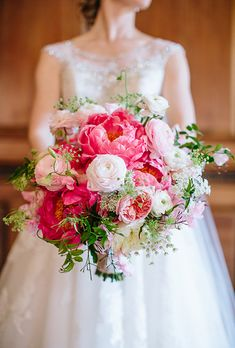 Brides.com: . Coral peonies were paired with ranunculus, garden roses, and Queen Anne's lace in this romantic bouquet, created by San Francisco florist Amy Burke Designs.