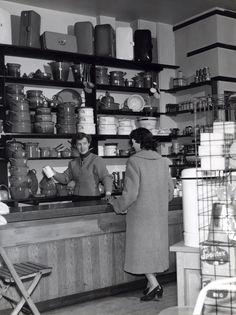 Een vrouw wordt door een verkoopster geadviseerd aan de toonbank van een winkel in keukenartikelen.Er worden onder andere broodtrommels, pannensets, emmers en vergieten enz verkocht.