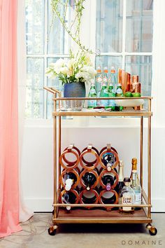 Gold bar cart with beautiful flowers and pink curtains