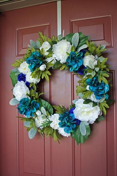 Floral Wreath Artificial white peonies, white ranunculus, teal hydrangeas, indigo corn flowers, lambs ear, and a beautiful assortment of artificial greenery are attached to a natural grapevine form. This would be perfect on your front door, mantel, or wall. The combination of flowers and greenery gives the wreath a very realistic look. This would also be a beautiful decoration or gift for a wedding or shower.  It measures approximately 24 (18 grapevine base)  There is a small wire hanger on…
