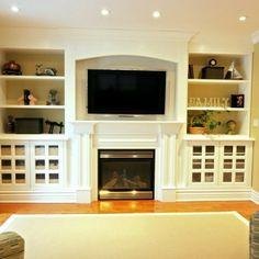 white shelving + fireplace + tv + lights
