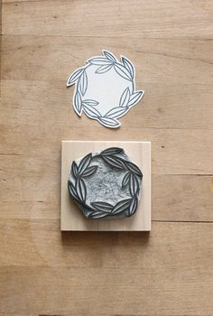 A sweet leafy wreath stamp hand-carved out of rubber. The stamp is mounted on a piece of sanded wood. It comes in a recycled plastic and cardboard package. Use it to decorate your own cards, decorative/wrapping papers, stationary, packaging, etc.! The possibilities are endless.. The stamp image measures approx. 1 3/4 x 1 3/4.