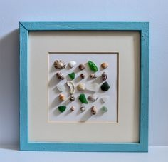 Use sea glass, pebble s and shells to create a beach art picture, click through to the blog for more information