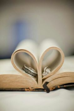 Make a heart shape with the Bible's pages and add rings to the centre.
