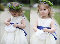 Daminha com coroa de flores na cabeça.