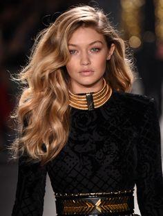 Gigi Hadid wears a black and metallic H&M Balmain ensemble.