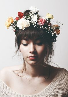 Flower crown is way too big, but I love the contrast of the straight line of her bangs with the organic shapes of the flowers and soft curls of her hair. I definitely would want more hair framing my face, than that, but this is a pretty good example of the fringe + cateye + general feel.
