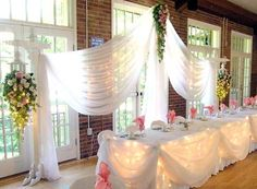 Decorating Dreams: Wedding decorating photos of indoor reception with natural light from windows, white, pink and green decorations and linens love the lights behind the table cover