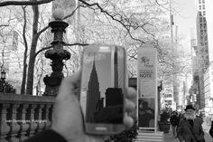 """""""Reflejo en la 42"""" -- A la altura de Bryant Park, logré captar el reflejo de edificio Chrysler en mi móvil mientras tomaba una vista general de la calle. La composición del totem y la farola del parque completan la sensación de verticalidad de la ciudad. El caballero con bombín y barbas """"firmó"""" la fotografía."""